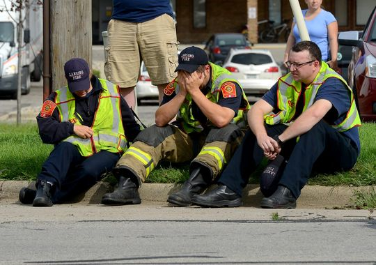 "Lansing firefighters sit on the curb on Cedar Street just north of Jolly Road Wednesday after a fellow firefighter was hit by a vehicle during the ""Fill the Boot"" collection campaign. (Photo: Dave Wasinger/Lansing State Journal)"